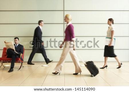 Profile shot of businesspeople walking in office corridor - stock photo