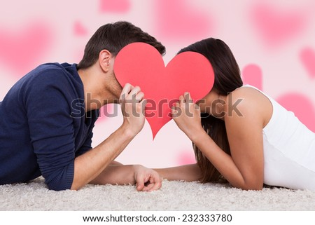 Profile shot of couple kissing behind heart while lying on fur - stock photo