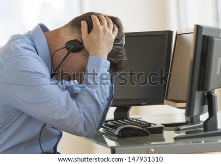Profile shot of male exhausted trader with head in hands leaning at computer desk in office - stock photo