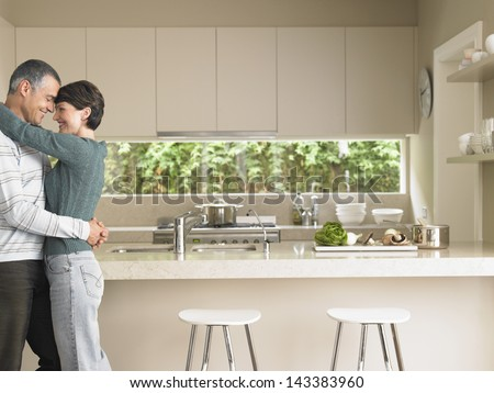 Profile shot of man and woman embracing in kitchen - stock photo