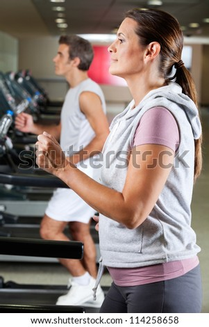 Profile shot of mature woman and man running on treadmill in health club - stock photo