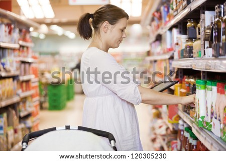 Profile shot of mid adult woman using digital tablet for shopping at supermarket - stock photo
