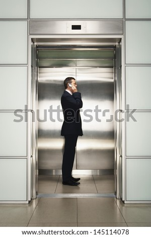 Profile shot of middle aged businessman using cellphone in elevator - stock photo