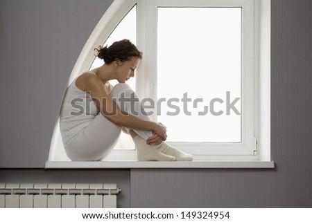 Profile shot of sad woman sitting on window sill - stock photo