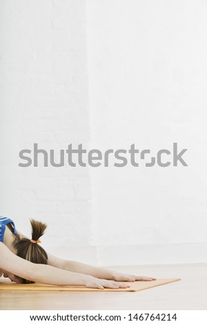 Profile shot of woman doing Seated Forward Bend in gym