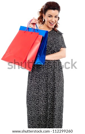 Profile shot of woman holding shopping bags isolated on white - stock photo