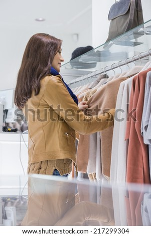Profile shot of woman selecting sweater in store - stock photo