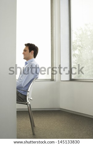 Profile shot of young businessman sitting on chair in office - stock photo