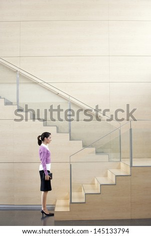 Profile shot of young businesswoman with diary standing in front of steps in office