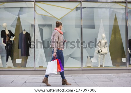 Profile shot of young woman with shopping bags looking at window display - stock photo