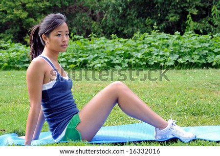 profile shout of attractive young Asian woman on fitness mat - stock photo