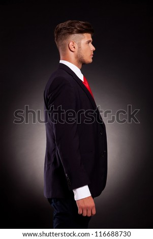 profile side view of a young attractive business man on dark background