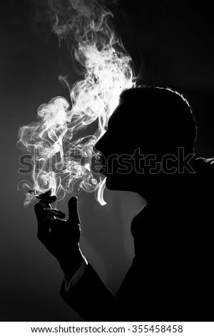 profile silhouette of a business man who smokes - stock photo