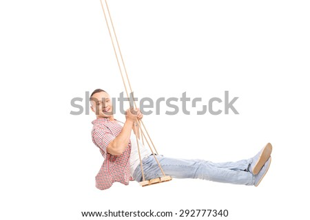 Profile studio shot of a delighted young man swinging on a wooden swing and looking at the camera isolated on white background - stock photo