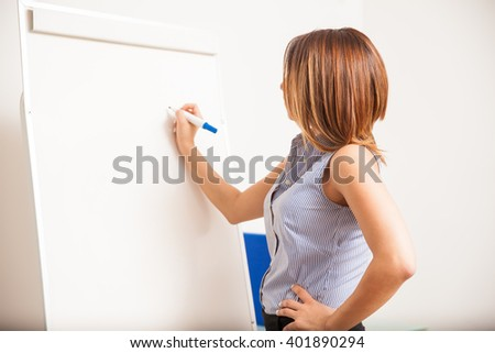 Profile view of a beautiful brunette writing on a flip chart during an English class - stock photo