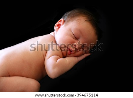 Profile view of a beautiful sleeping newborn baby on a black background - stock photo
