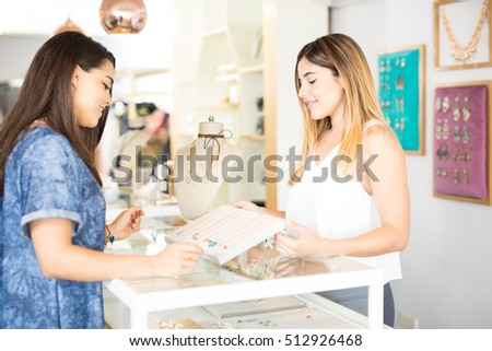 Profile view of a beautiful young salesperson standing in front of a client at a jewelry and fashion store