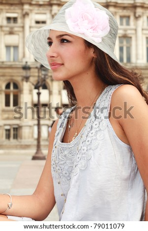 Profile view of a beautiful young woman enjoying the sights of a Parisian plaza. - stock photo