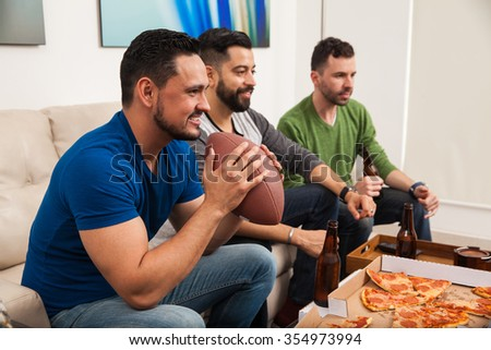 Profile view of a bunch of guys watching an american football game on TV while eating pizza and drinking some beer - stock photo