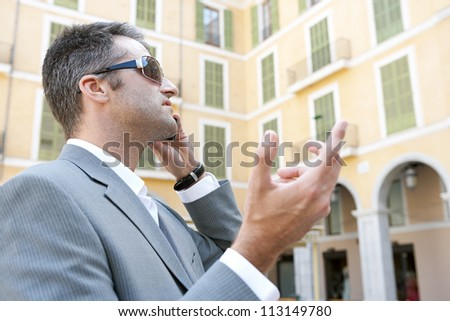 Profile view of a businessman using a smart phone to have a conversation while standing in front of classic office buildings in the city. - stock photo