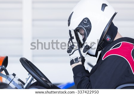 profile view of a concentrated karting pilot sitting on his go-kart before starting a race in an outdoor go karting circuit - focus on the eye - stock photo