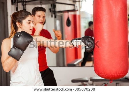Profile view of a cute young brunette getting boxing lessons from a man at the gym - stock photo