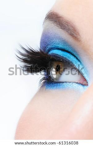 Profile view of a female eye with bright blue  make-up and long black false eyelashes - stock photo