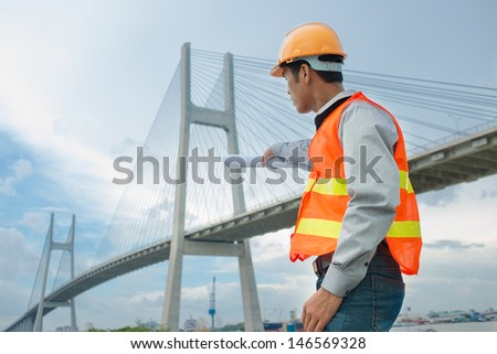 Profile view of a foreman thinking about bridge reconstruction outside