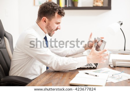 Profile view of a furious businessman yelling at his laptop computer in frustration for its malfunctioning - stock photo