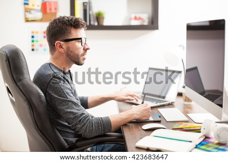 Profile view of a good looking Hispanic young man multitasking at work, using two computers at once