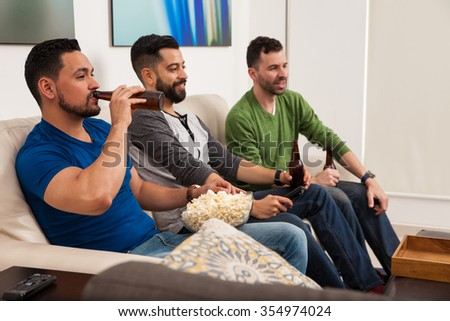 Profile view of a group of three male friends relaxing in the living room while drinking beer and eating snacks - stock photo