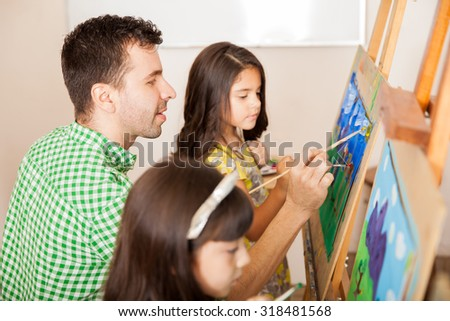 Profile view of a handsome art teacher working on a painting with one of his students in class - stock photo