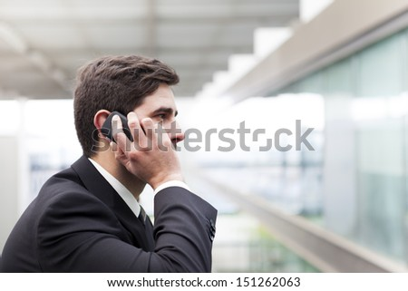 Profile view of a handsome young business man talking on cell phone