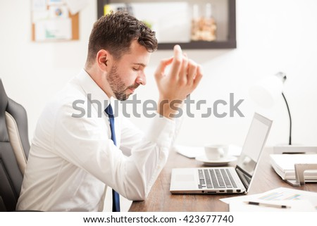 Profile view of a handsome young man doing some meditation exercises while working at the office - stock photo