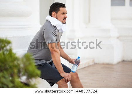 Profile view of a handsome young man with a beard resting and drinking some water after exercising in the city - stock photo