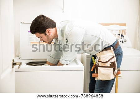 Profile view of a male technician inspecting and fixing a washer and dryer in a laundry room