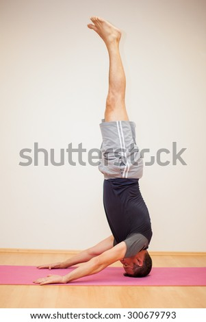 Profile view of a man doing a headstand and maintaining balance in a yoga studio