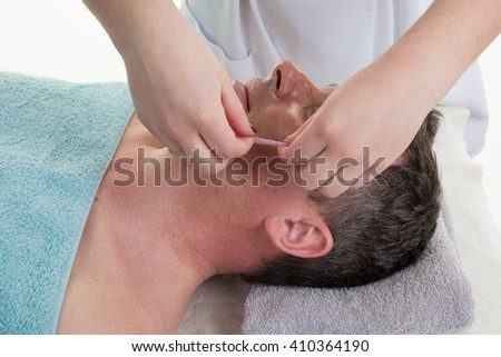 Profile view of a man with facial mask in beauty salon - stock photo