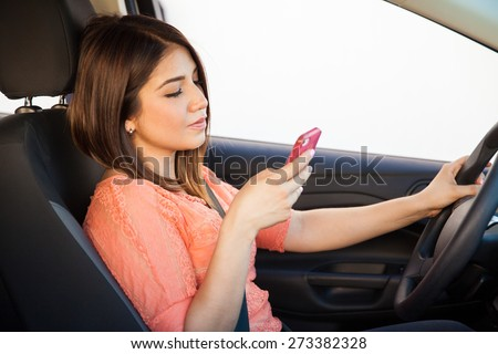 Profile view of a reckless Latin young woman using a smartphone while driving a car - stock photo