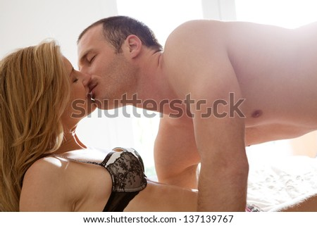 Profile view of a sexy and attractive couple being passionate and kissing in bed in intimacy, with sun rays filtering into the room.