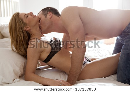 Profile view of a sexy and attractive couple being passionate and kissing in bed while wearing jeans and lingerie.