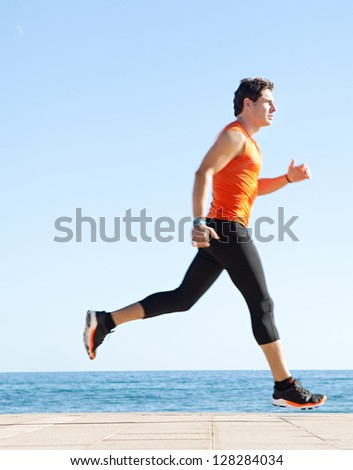 Profile view of a sports man running figure on a track along the sea with the blue sky in the background and space around him. - stock photo