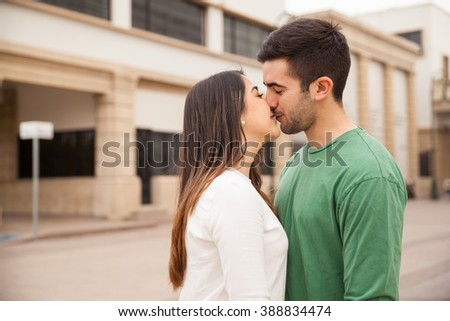 Profile view of a very young couple kissing each other outdoors