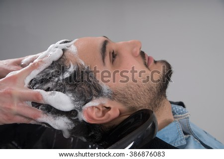 Profile view of a young arabic man getting his hair washed and his head massaged in a hair salon