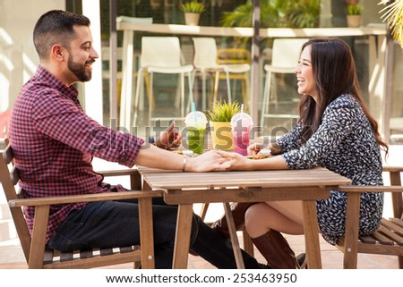 Profile view of a young couple holding hands during a lunch date and having fun - stock photo