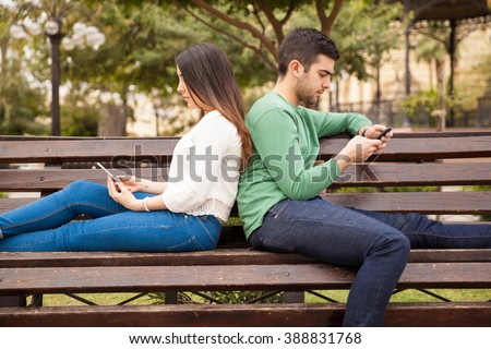 Profile view of a young couple sitting back to back and using their smartphones while ignoring each other - stock photo