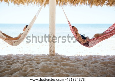 Profile view of a young couple sleeping in side by side hammocks during their vacation at the beach - stock photo