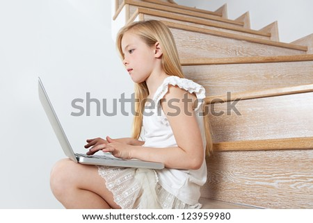 Profile view of a young girl child using a laptop computer while sitting down on her home's wooden steps. - stock photo