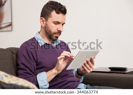 Profile view of a young handsome man with a beard using a tablet computer while sitting on a couch at home - stock photo