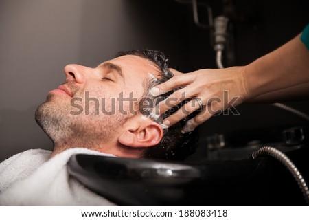 Profile view of a young man getting his hair washed and his head massaged in a hair salon - stock photo